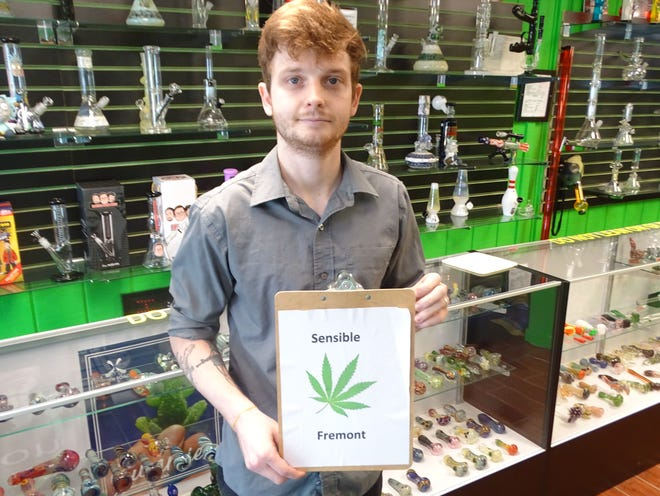 Joe Linder holds a sign for Sensible Fremont Thursday at the Hookah Connection. Sensible Fremont has put a proposed ordinance on the November ballot to change the eliminate fines and court costs for misdemeanor marijuana offenses in Fremont.