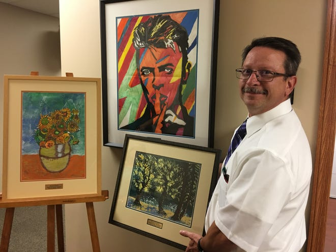 Superintendent Jon Detwiler reviews the Avenues in Art winners.