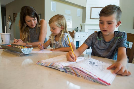 Harlow Rossi, 5, works on a picture with her mother Brittany while her older brother Camden, 8, works in a workbook on Thursday, Aug. 9, 2018, at the Rossi's home in Fort Collins, Colo. Harlow will be starting kindergarten at Zach Elementary School this Fall.