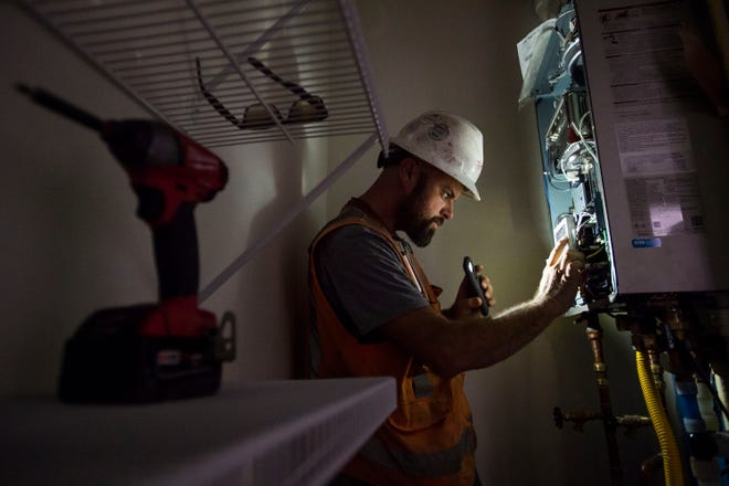 Lind's Plumbing & Heating foreman Jesse Ennen checks the operation of a newly-installed hydronic water heating system of a recently constructed apartment on Thursday, Aug. 9, 2018, at Housing Catalyst's low-income housing project at West Horsetooth Road and South Shields Street in Fort Collins, Colo.