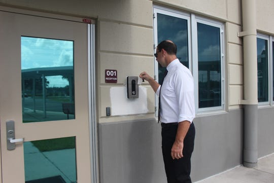 South Fort Myers High School Principal Ed Mathews put his identification in front of a camera positioned at the outside school's office