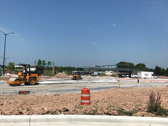 The Main Avenue-Lawrence Drive roundabout construction has fallen behind schedule. The gray building frame in the background is the new Aldi grocery store.