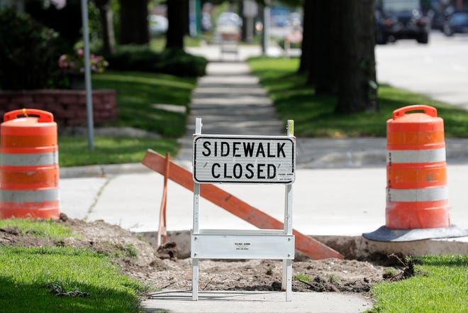 A sidewalk under repair is shown on Dousman St on Wednesday, August 8, 2018 in Green Bay, Wis.