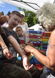 Cole David Goerts of Clarks Mills gets a glitter tattoo of a dragon from Erika Williams of Milwaukee in the arts and crafts fair at last year's Shanty DAys in Algoma.