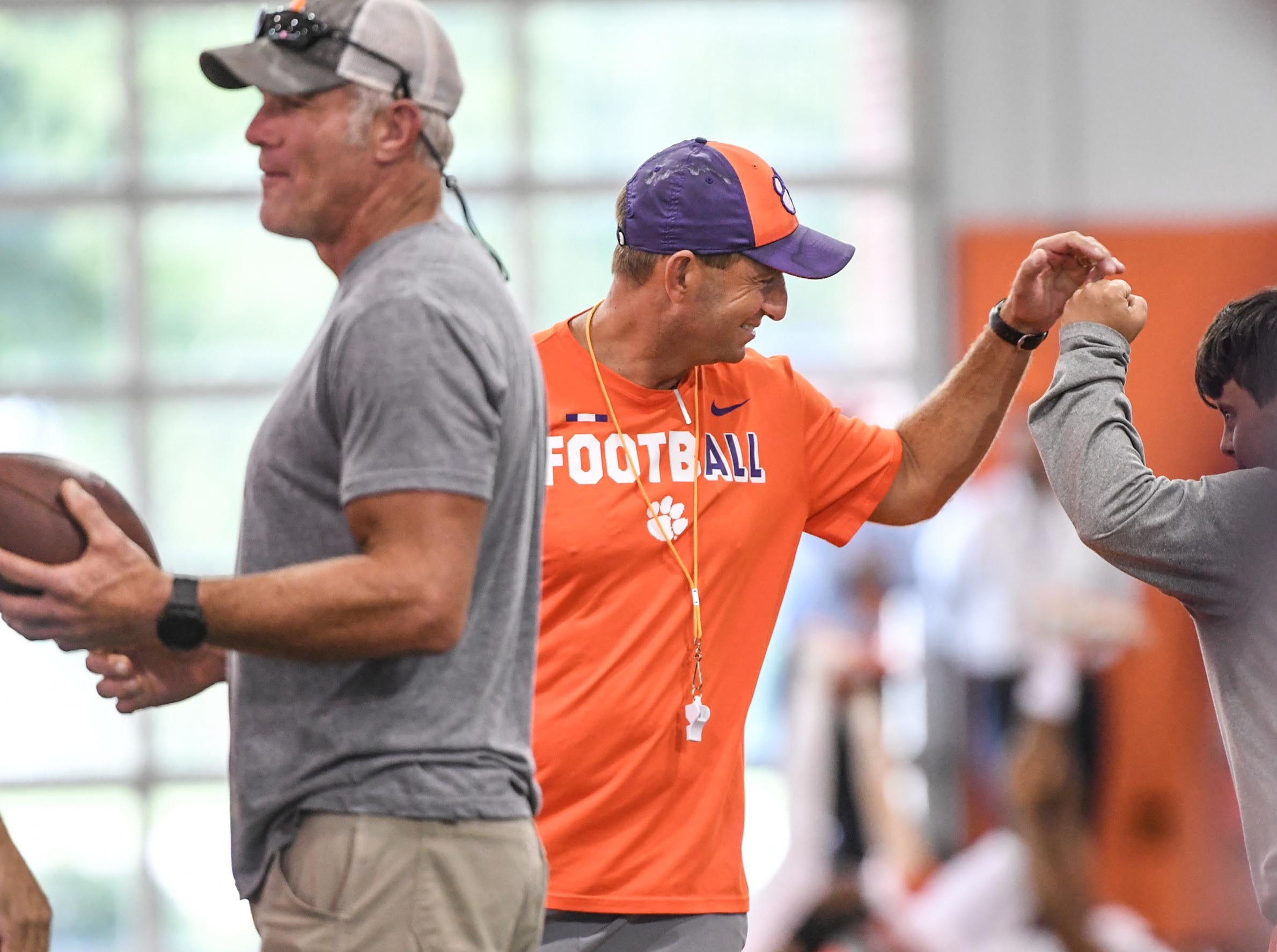 Brett Favre, left, stands near Clemson head coach Dabo Swinney fist bumping Dave Saville during fall practice in Clemson on Wednesday.