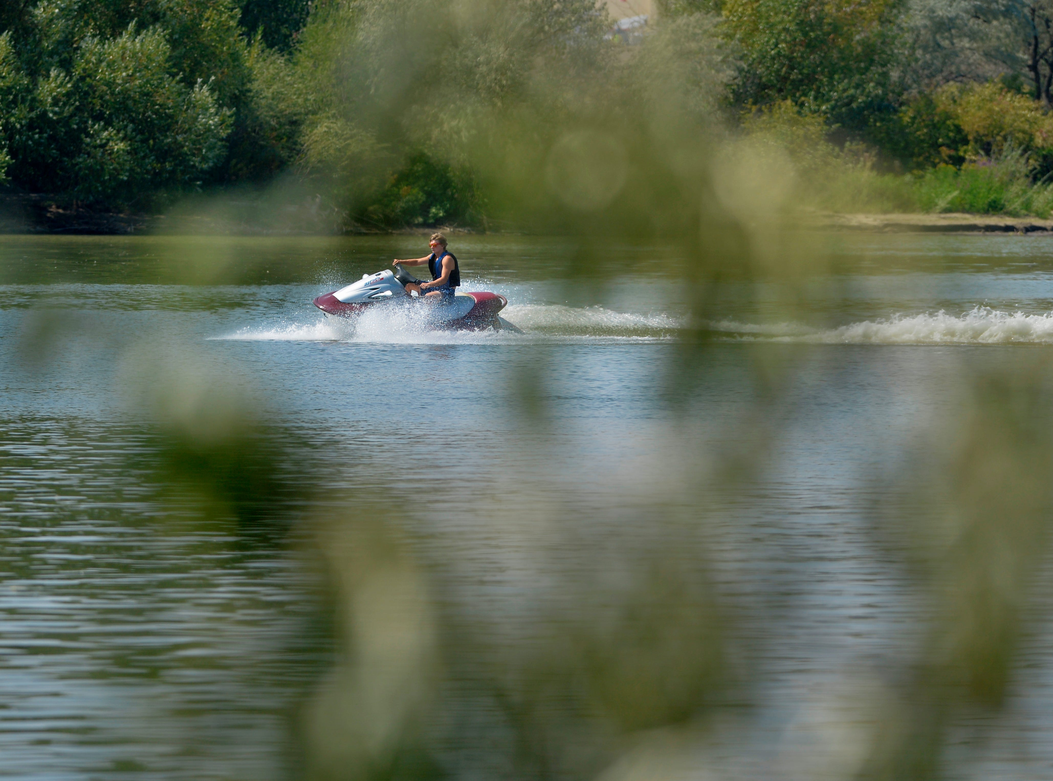 A boater on a personal watercraft enjoys zipping around Broadwater Bay, Thursday afternoon as temperatures approach 100 degrees.