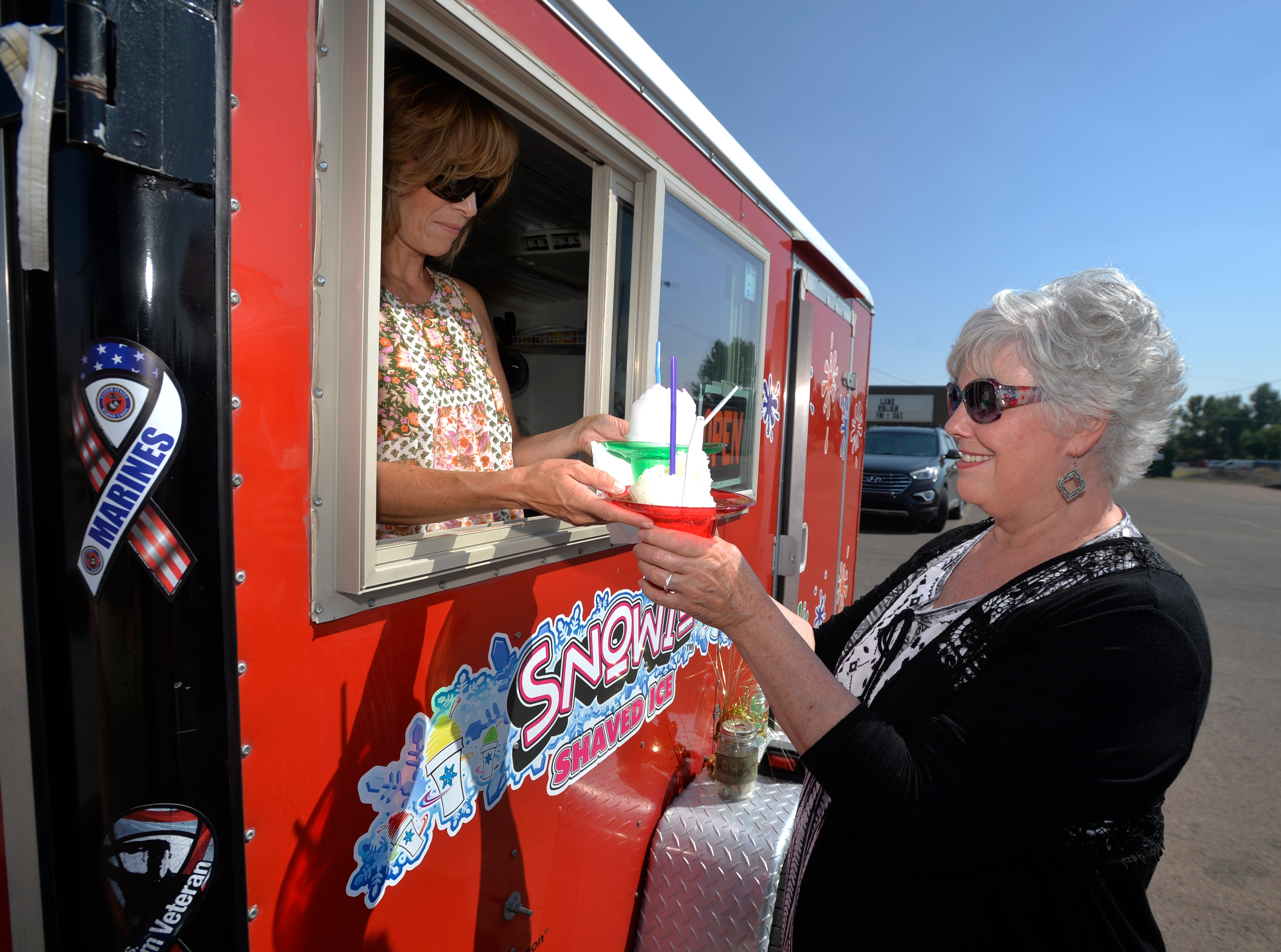 Noreen Langendorff stops for shave ice from the Snowie Shaved Ice stand on the 3000 block of 10th Avenue South, Thursday.