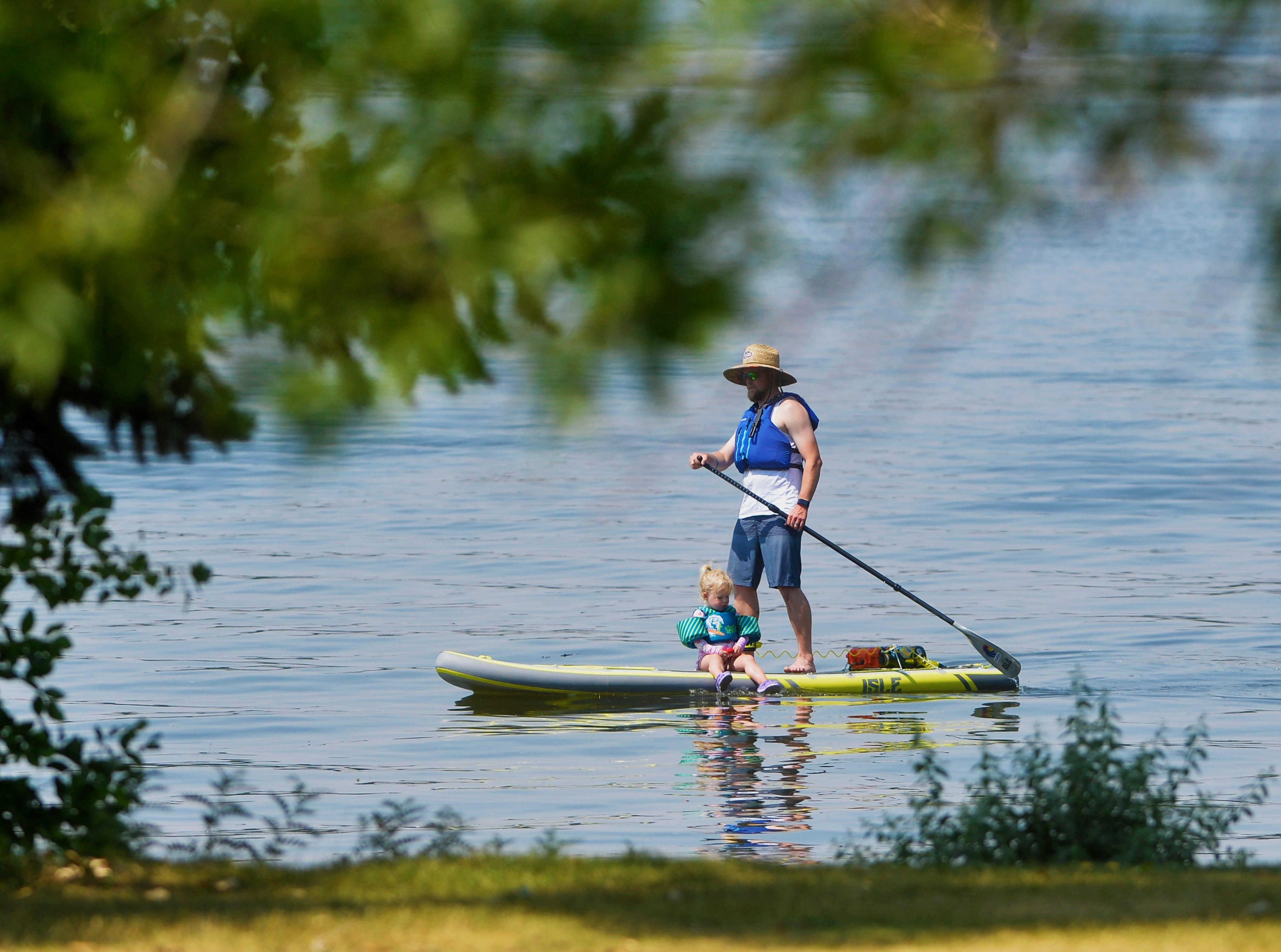 Luke Taylor paddle boards with his daughter Paizley, age 2, in Broadwater Bay on Thursday as temperatures approach 100 degrees.