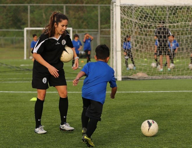 "Anjelica Perez, in all black, conducts a training session during a training session of the Spring 2018 cycle of the United Airlines GFA Center of Excellence, a program for elite youth athletes supported by Japan Football Association. Perez will take part in an upcoming AFC ""B"" Coaching Certificate Course set to begin Friday at the Guam Football Association National Training Center."
