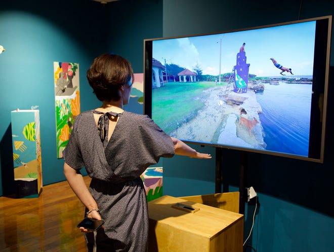 A guest at the Guam Eco Wave exhibition interacts with a virtual reality 360-degree exhibit display of a ko'ko' mural at Inarajan natural pools.