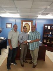 Keith Hattig of the Guam Islanders Softball Association and Charlie Hermosa, general manager of American President Lines Guam, present a donation to Piti Mayor Jesse Alig to cover the cost of supplies for electrical repairs at the Santos Park, which hosted the APL Women's Fastpitch League in July. From left: Hattig, Hermosa and Alig.