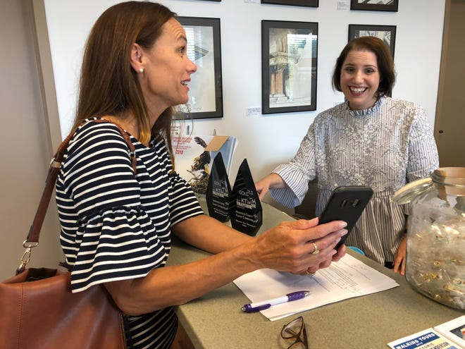 Flight attendant Pam Wofford, left, shows Downtown Henderson Partnership administrative assistant Heather Salisbury a photo on her smartphone. The two Henderson women are each both the wife and daughter of a church pastor.