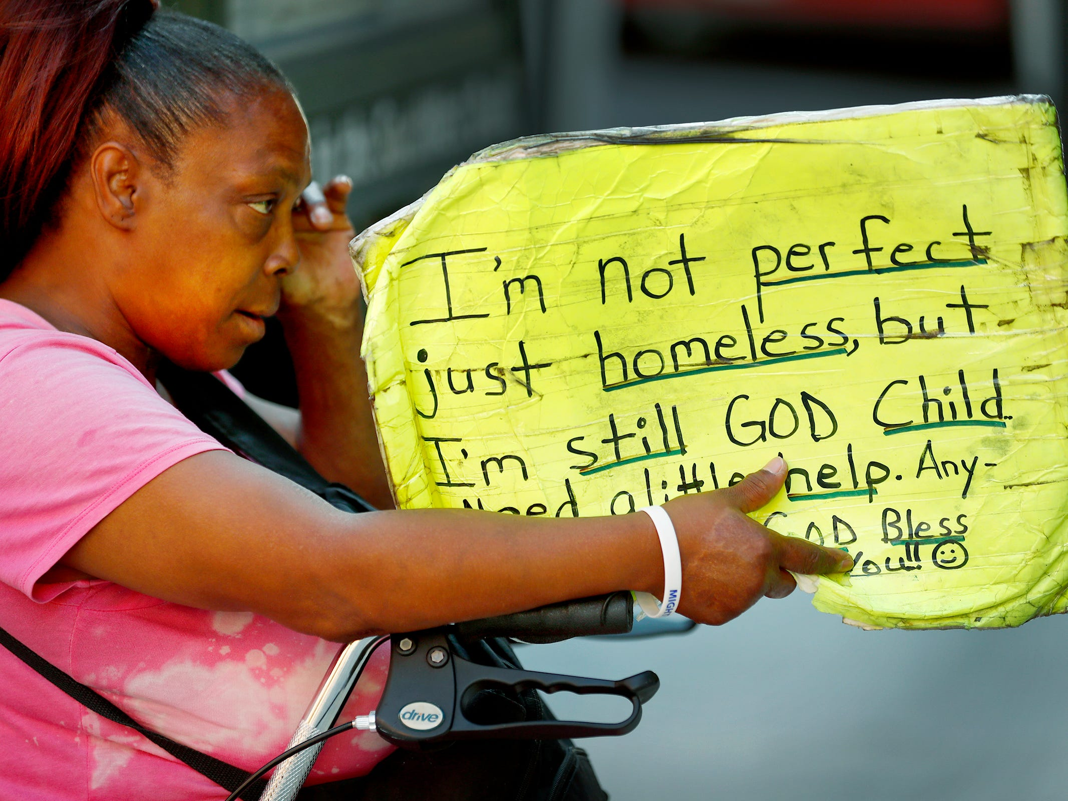 Regina Gilbert, a homeless woman in downtown Indianapolis, rubs her eye as she holds a sign asking for some help, Thursday, Aug. 9, 2018.  Coalition for Homelessness Intervention & Prevention (CHIP) and the city of Indianapolis have proposed a plan to end homelessness in the city by 2023.