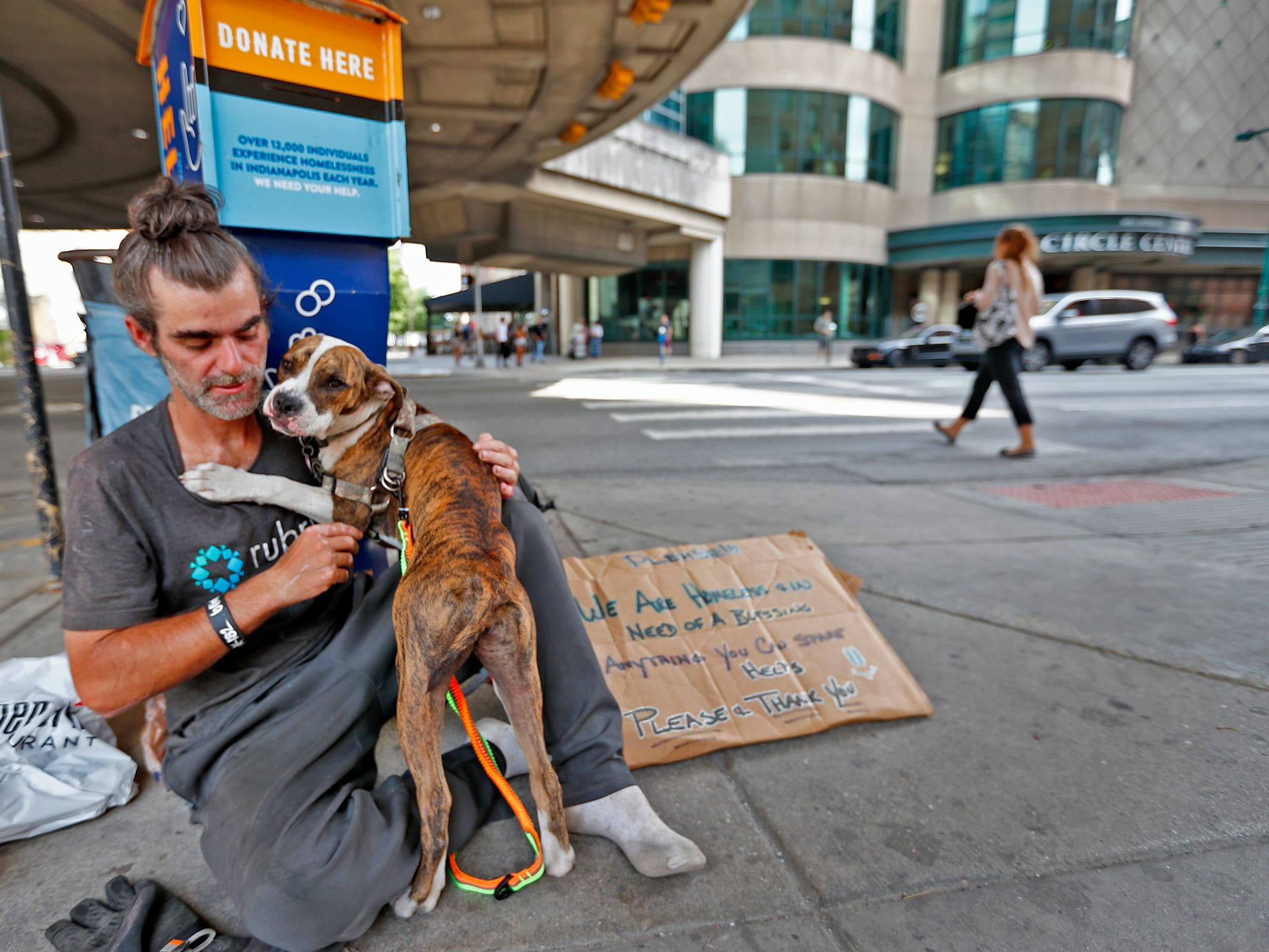 A homeless man and his dog hang out on a corner in downtown Indianapolis, Thursday, Aug. 9, 2018.  Coalition for Homelessness Intervention & Prevention (CHIP) and the city of Indianapolis have proposed a plan to end homelessness in the city by 2023.