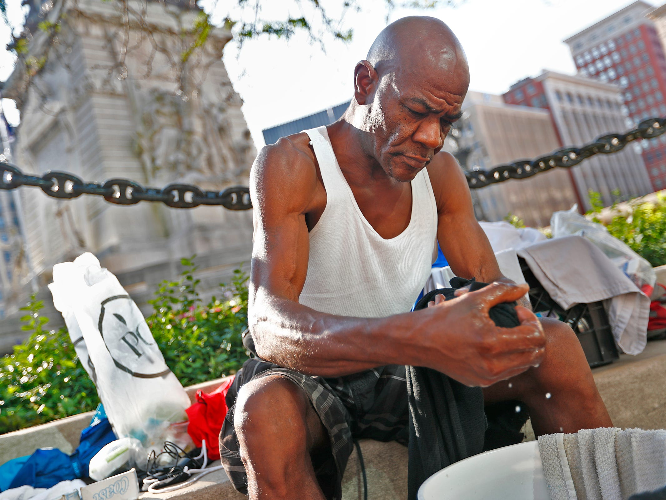 "Glenn Hudgins, a homeless man, does his laundry on Monument Circle, in downtown Indianapolis, Thursday, Aug. 9, 2018.  He says he has been homeless for about 4 years.   ""Everyone knows me, in a good way,"" he says about keeping himself clean, doing work when offered, and staying away from drink and drugs.  Coalition for Homelessness Intervention & Prevention (CHIP) and the city of Indianapolis have proposed a plan to end homelessness in the city by 2023."