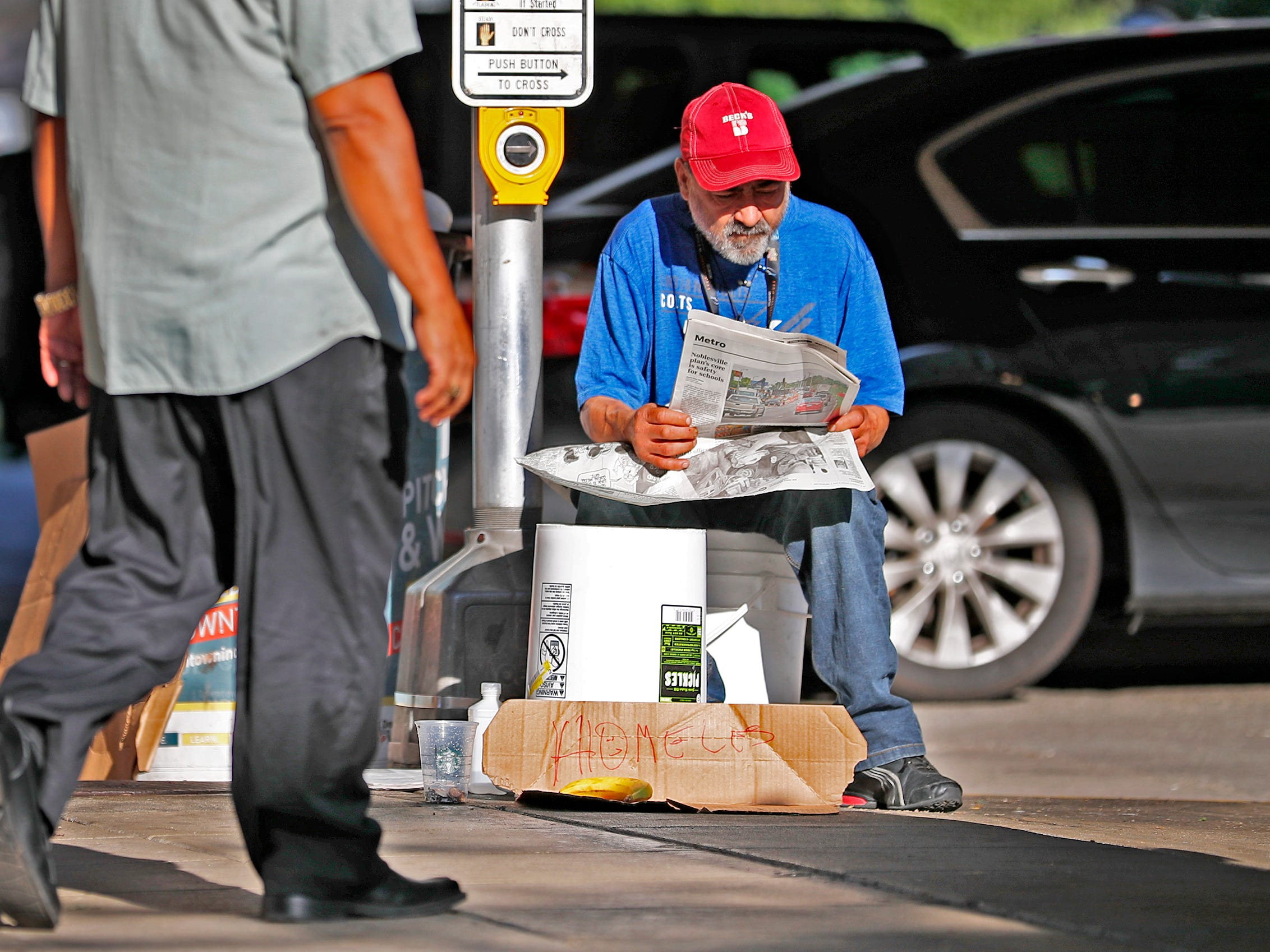 Roberto Green, a homeless man, reads the newspaper while he waits for handouts in downtown Indianapolis, Thursday, Aug. 9, 2018.  He says he is waiting for disability.  Coalition for Homelessness Intervention & Prevention (CHIP) and the city of Indianapolis have proposed a plan to end homelessness in the city by 2023.