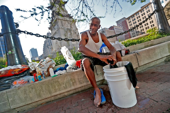 """Glenn Hudgins, a homeless man, does his laundry on Monument Circle, in downtown Indianapolis, Thursday, Aug. 9, 2018.  He says he has been homeless for about 4 years.   """"Everyone knows me, in a good way,"""" he says about keeping himself clean, doing work when offered, and staying away from drink and drugs.  Coalition for Homelessness Intervention & Prevention (CHIP) and the city of Indianapolis have proposed a plan to end homelessness in the city by 2023."""