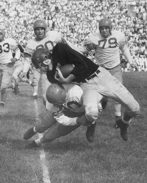In this action shot from the third annual City High School Football Jamboree on Sept. 11 1954 Broad Ripple's Ken Long (bottom) brings down junior fullback Ronnie Sherbert of Shortridge at the 45-yard line  before an estimated crowd of 8,000 at Butler Bowl.