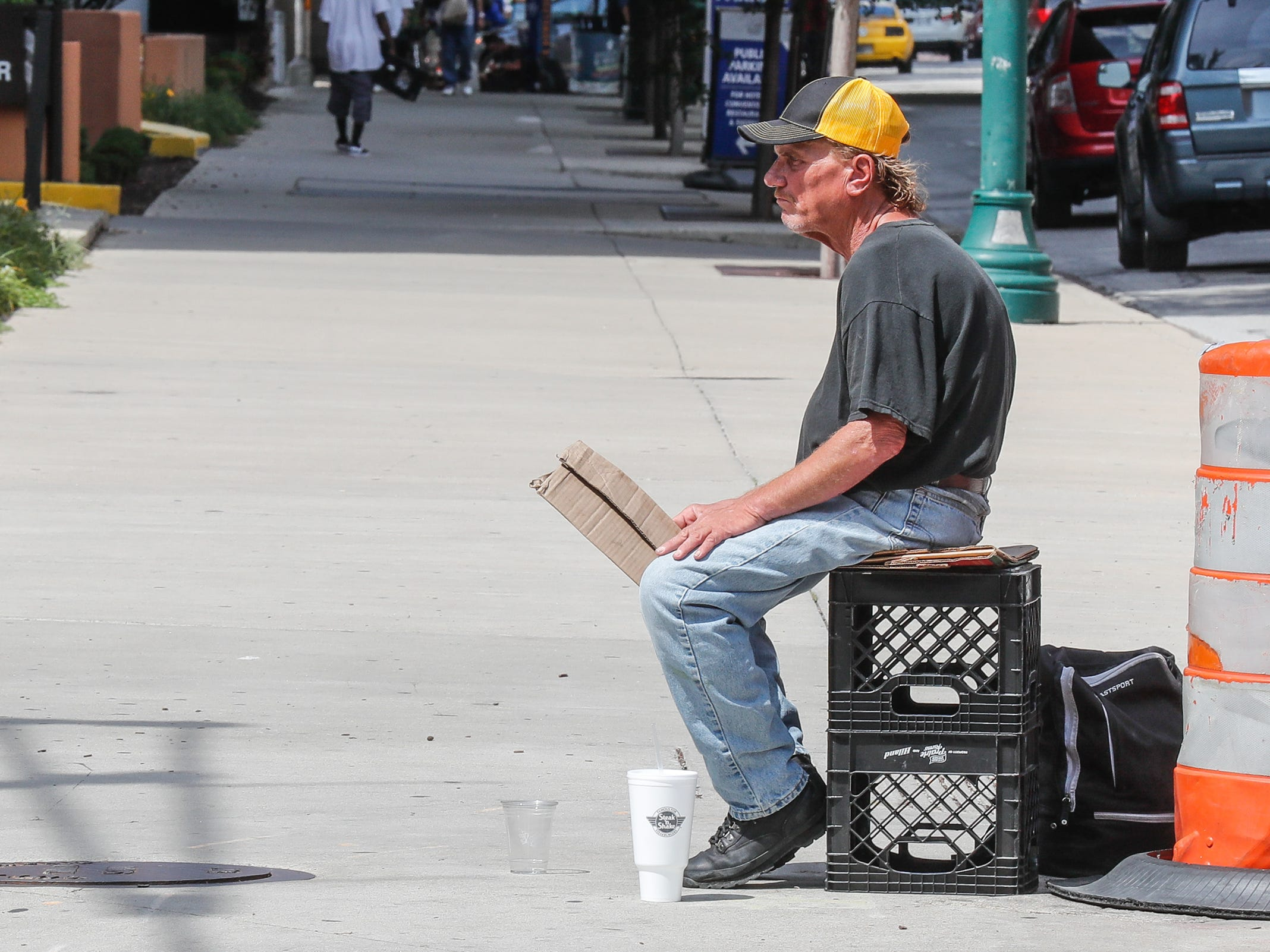 A man begs for money on a street corner in Indianapolis on Thursday, Aug. 9.2018.