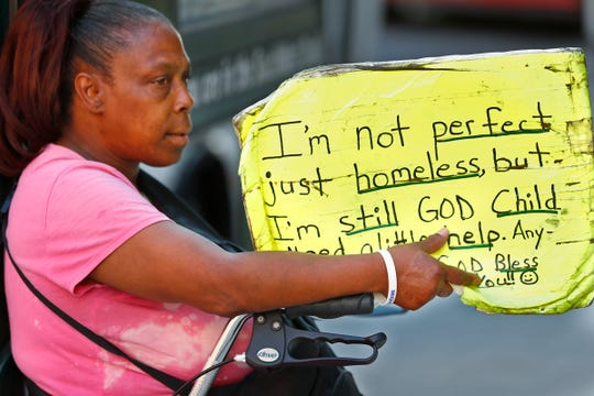 Regina Gilbert, a homeless woman in downtown Indianapolis, holds a sign asking for some help, Thursday, Aug. 9, 2018.  Coalition for Homelessness Intervention & Prevention (CHIP) and the city of Indianapolis have proposed a plan to end homelessness in the city by 2023.