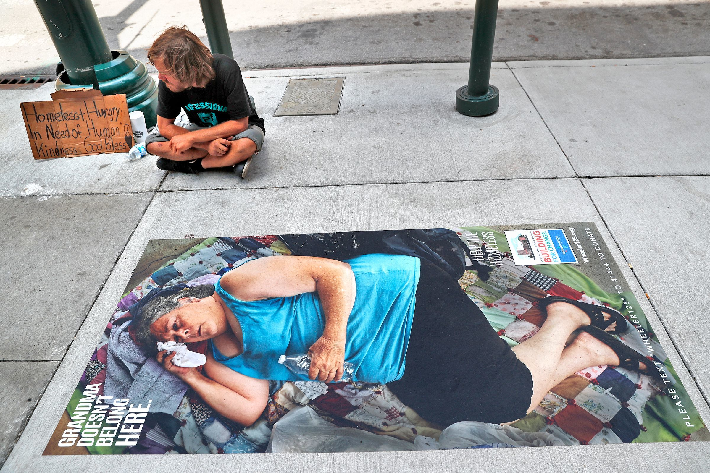 A homeless man sits by a new Wheeler Missions life-size sidewalk photo of a homeless woman, at the corner of Maryland and Illinois, in downtown, Tuesday, July 10, 2018. Wheeler Mission has launched a multi-million dollar campaign to triple the size of its Women and Children's Shelter. Part of the awareness campaign includes 20 such pieces of sidewalk art.