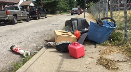Trash from an abandoned house is piled on the sidewalk on South Walcott Street.