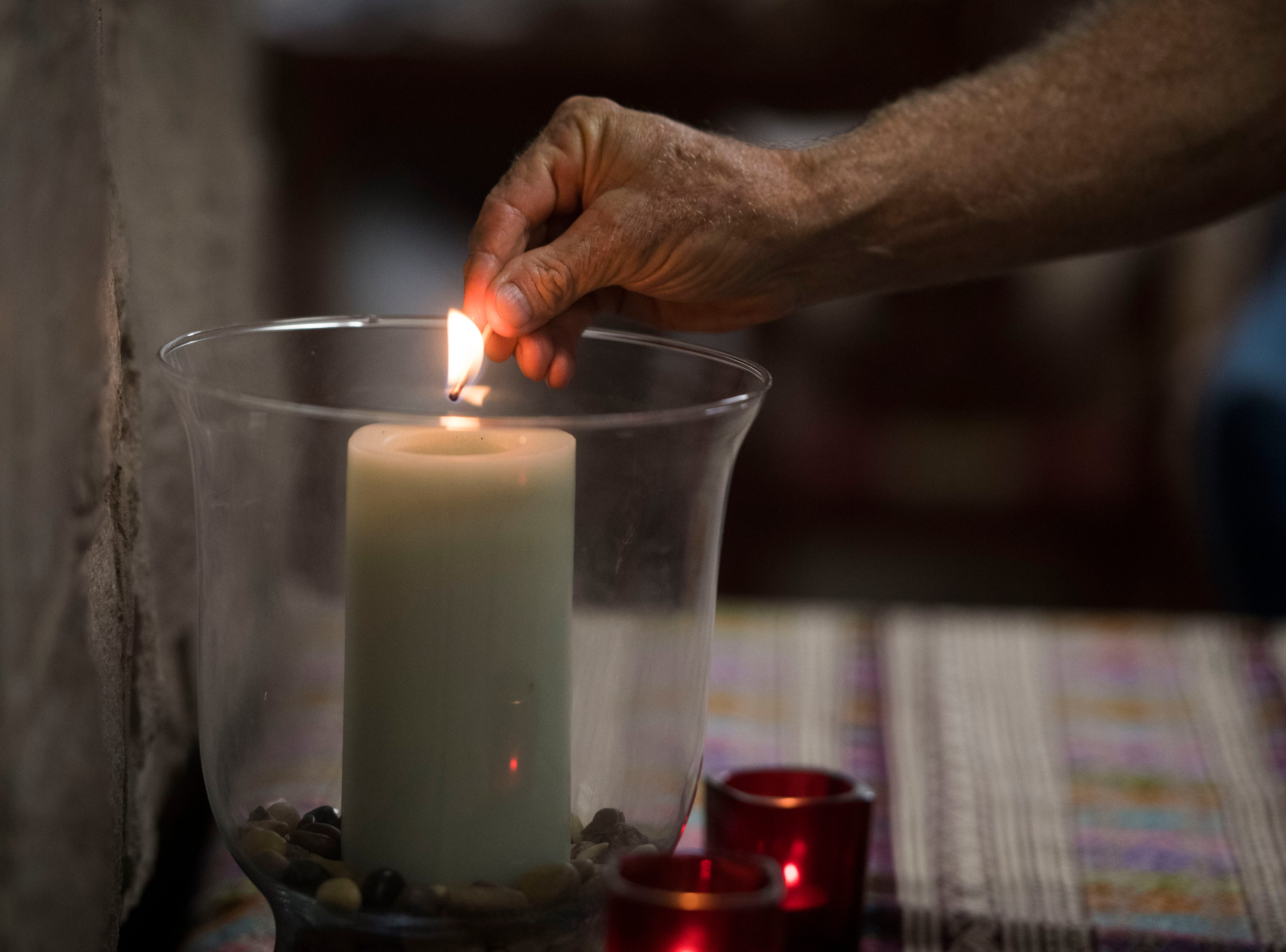 Ralph Hutchinson of Knoxville, with Tennesseans for Alternatives to the Death Penalty, lights a candle at a vigil opposing the execution of Billy Ray Irick at the Shalom House at Church of the Savior in West Knoxville, Thursday, Aug. 9, 2018.