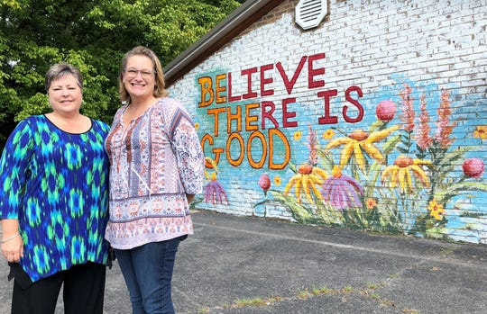 """Monica Lauber (right) and wife Amy Perkins outside The Village Mercantile at 4503 Walker Blvd. The mural on the side of the store is a recent addition and is part of an ongoing barter deal with artist Christian Freeman Creations. """"I grew up in southern California where mural art is very important and always dreamed of having a space for a mural,"""" said Lauber. """"There's still some work to be done on it, but we are gaining on it. We wanted to brighten the building to remember that there is good in the world."""""""