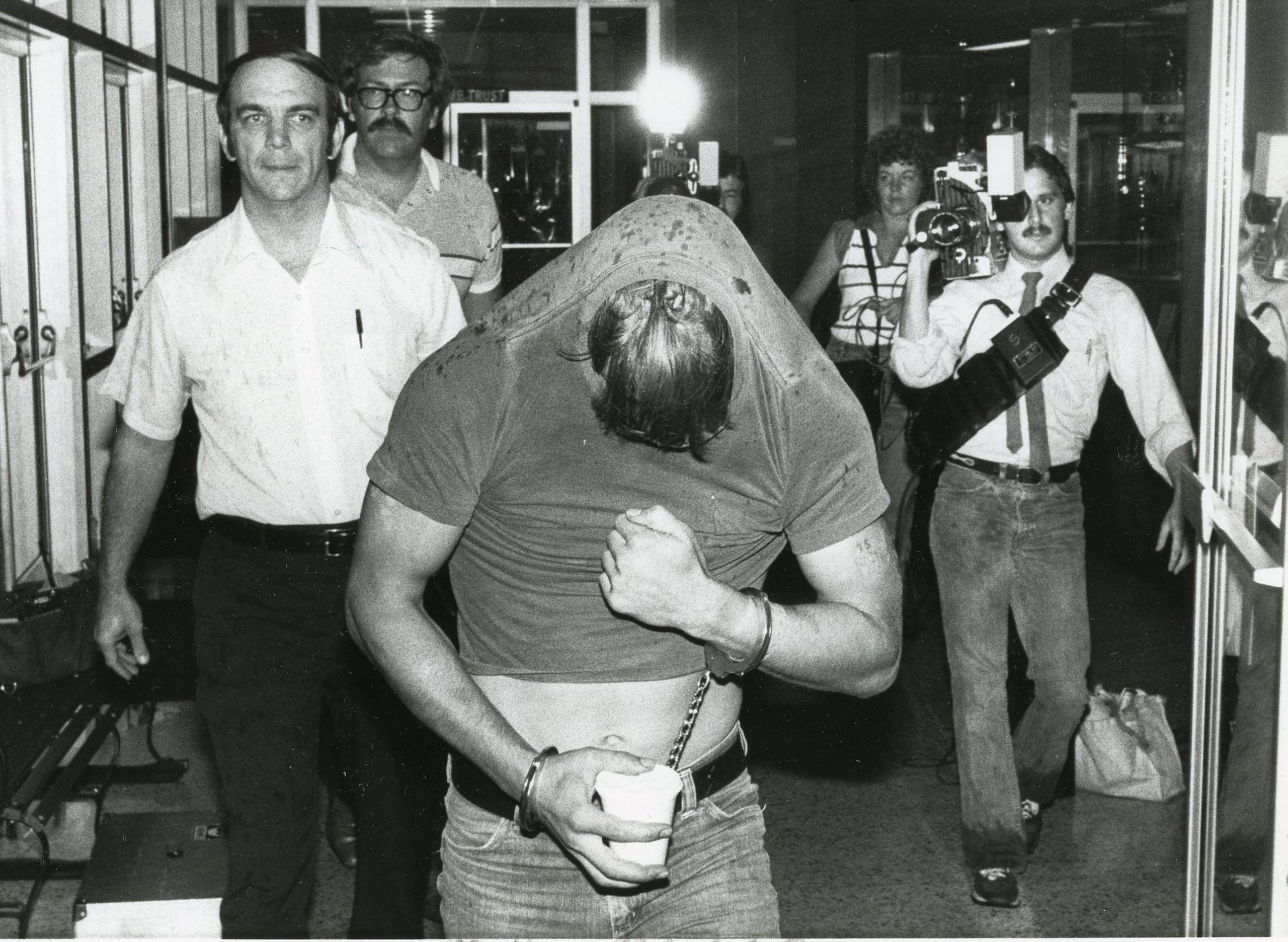 David Earl Miller covers his face with his shirt in this News Sentinel archive photo.