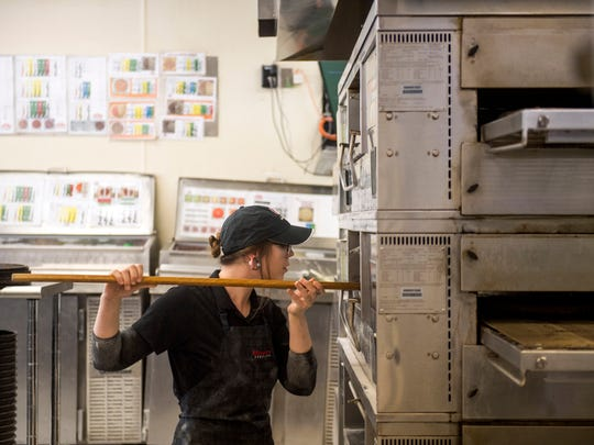 Sydney Hamlet checks on the pizzas in the oven during a practice run on Monday, Aug. 7, 2018, for the Papa John's Global Pizza Games. Team Home Run, based out of the Knoxville Papa John's location at 1819 Lake Ave., will be among the six teams competing.