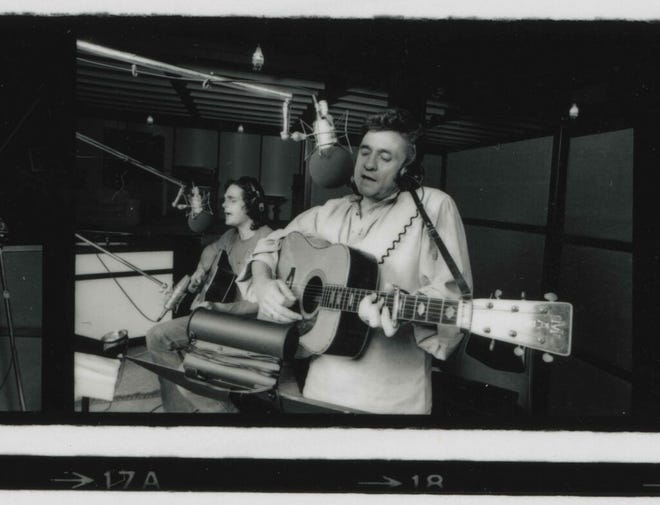 In this photo from the mid-'70s, Jack Routh, left, plays in the studio with Johnny Cash.