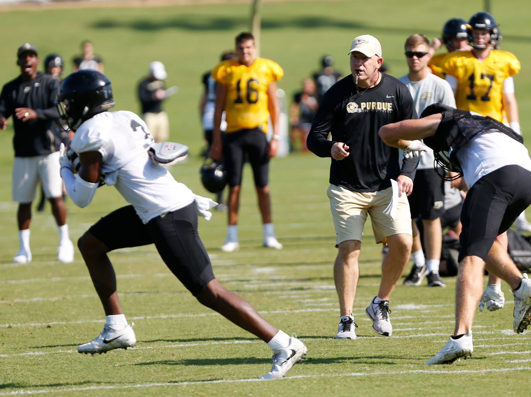 Head coach Jeff Brohm looks on as cornerback Kamal Hardy, left, strips the ball from wide receiver Kory Taylor during Purdue football practice Thursday, August 9, 2018, in West Lafayette.
