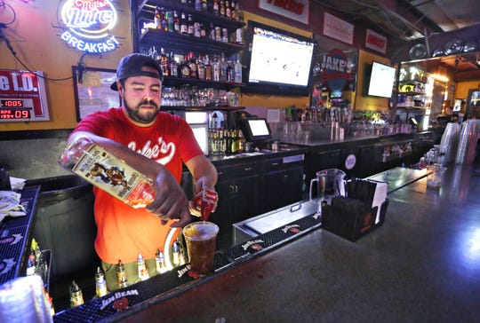 General manager Jose Fogleman, who worked at the bar for over 17 years, mixes a drink at Jake's Roadhouse. The bar announced it had closed it's doors for good on Wednesday evening after a rough summer of business.