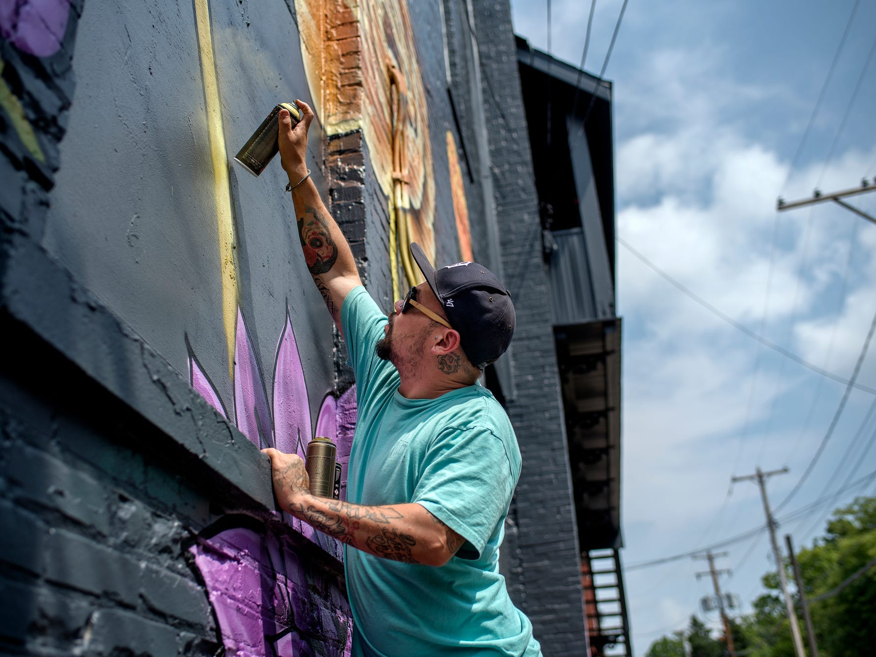 Chris Garcia, 34, of Holland, paints a mural on the side of Kean's Store on Thursday, Aug. 9, 2018, in downtown Mason. His murals are done in graffiti-style with spray can paints.