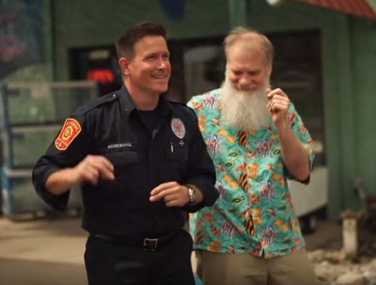 """Jim Harrington, of the Lansing Fire Department, and Rick Preuss, of Preuss Pets, dance in a scene of the """"Can't Stop the Feeling"""" video promoting Lansing."""