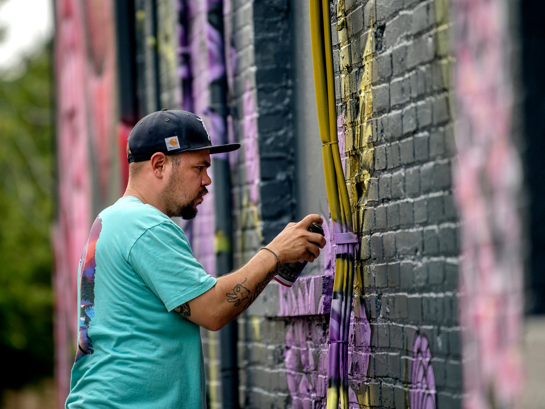 Chris Garcia, 34, of Holland, paints a mural on the side of Kean's Store on Thursday, Aug. 9, 2018, in downtown Mason.