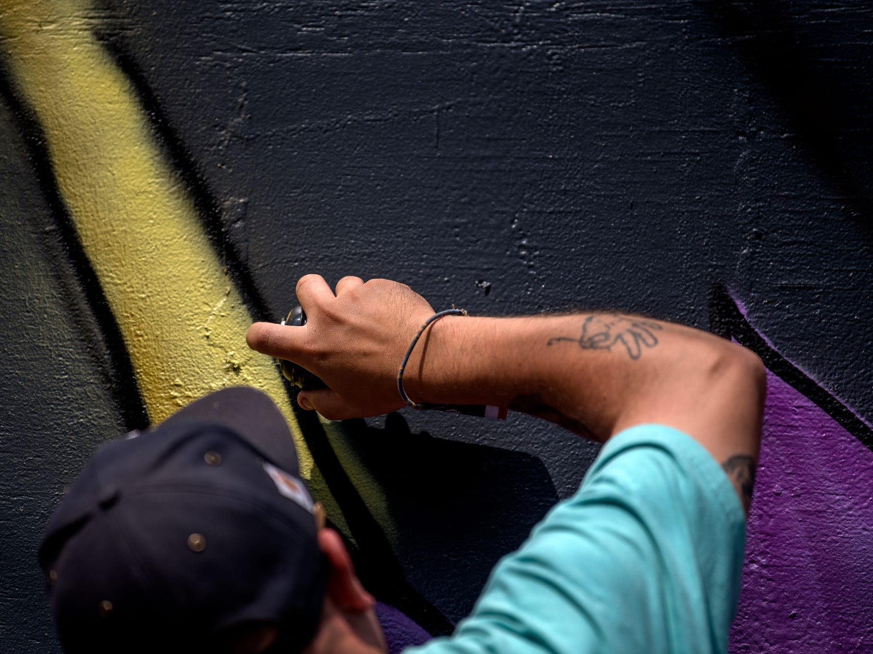 Chris Garcia, 34, of Holland, works on the outline of a flower stem as he paints a mural on the side of Kean's Store on Thursday, Aug. 9, 2018, in downtown Mason. Garcia has been working on the piece over the course of the week.