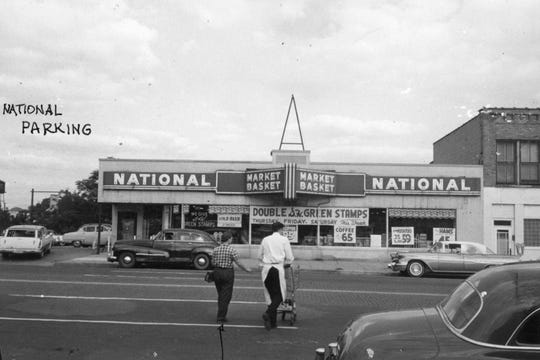 National Foods was directly across North Washington Avenue from the A&P Foodstore. City Planning Division staff annotated the photo including the arrow drawn pointing to a woman walking beside a store clerk pushing a grocery cart.
