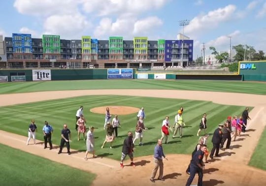 """Participants in the """"Can't Stop the Feeling"""" video dance on the Cooley Law School Stadium field in downtown Lansing."""