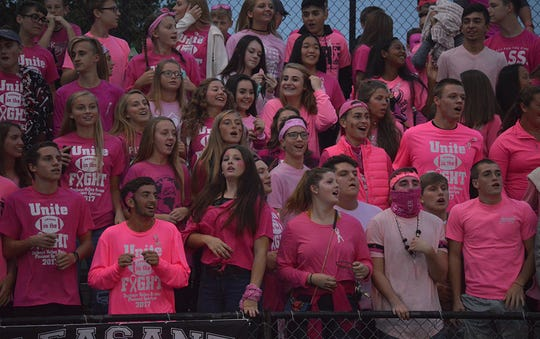 The Pleasant student section gets excited during a football game last season.