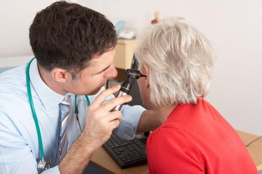 British Doctor Examining Senior Woman S Ear