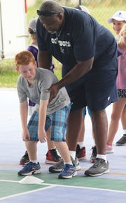 Steve Grant gives camper Tebow Morris some advice on balance control before a play.