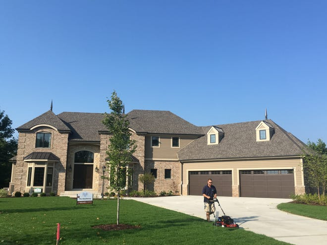 Andy Oppermann, operations manager for MJS Landscaping Services, mows the lawn Thursday on a Parade of Homes property at Lilly Crossing in Brookfield.