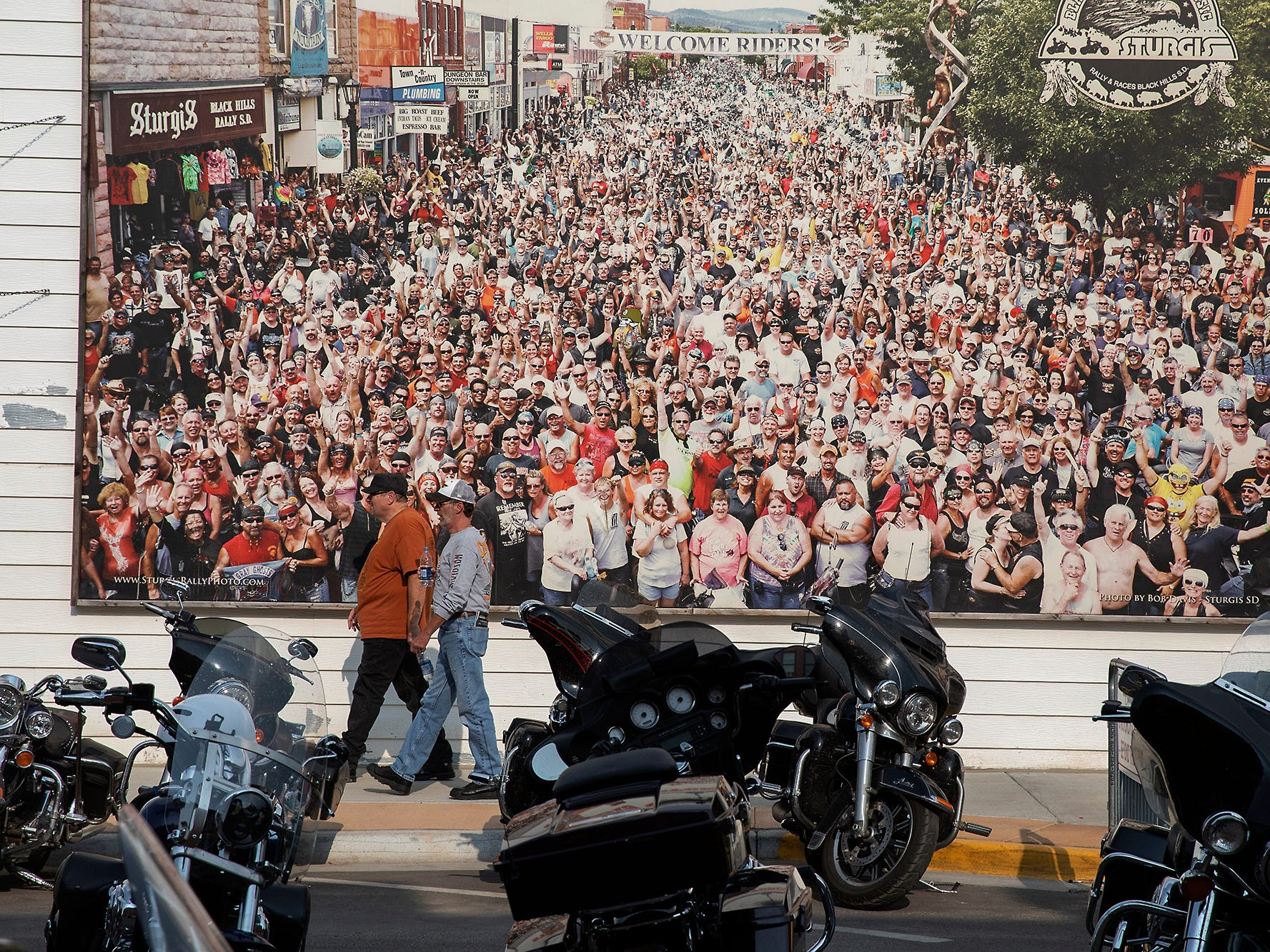 2018: People walk past a large print of a photograph taken during a previous motorcycle rally in downtown Sturgis, S.D.