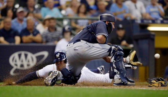 Milwaukee's Jonathan Schoop slides in safely ahead of the throw to San Diego catcher A.J. Ellis during the fourth inning Thursday at Miller Park.