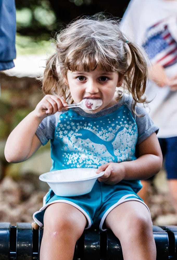 Three-year-old Noor Elkadri of Brookfield gobbles down a bowl of ice cream during the Brookfield Public Library's Ice Cream Social on Tuesday, August 7, 2018. The free event, sponsored by Friends of the Library, celebrates the end of Summer Reading with ice cream and music.