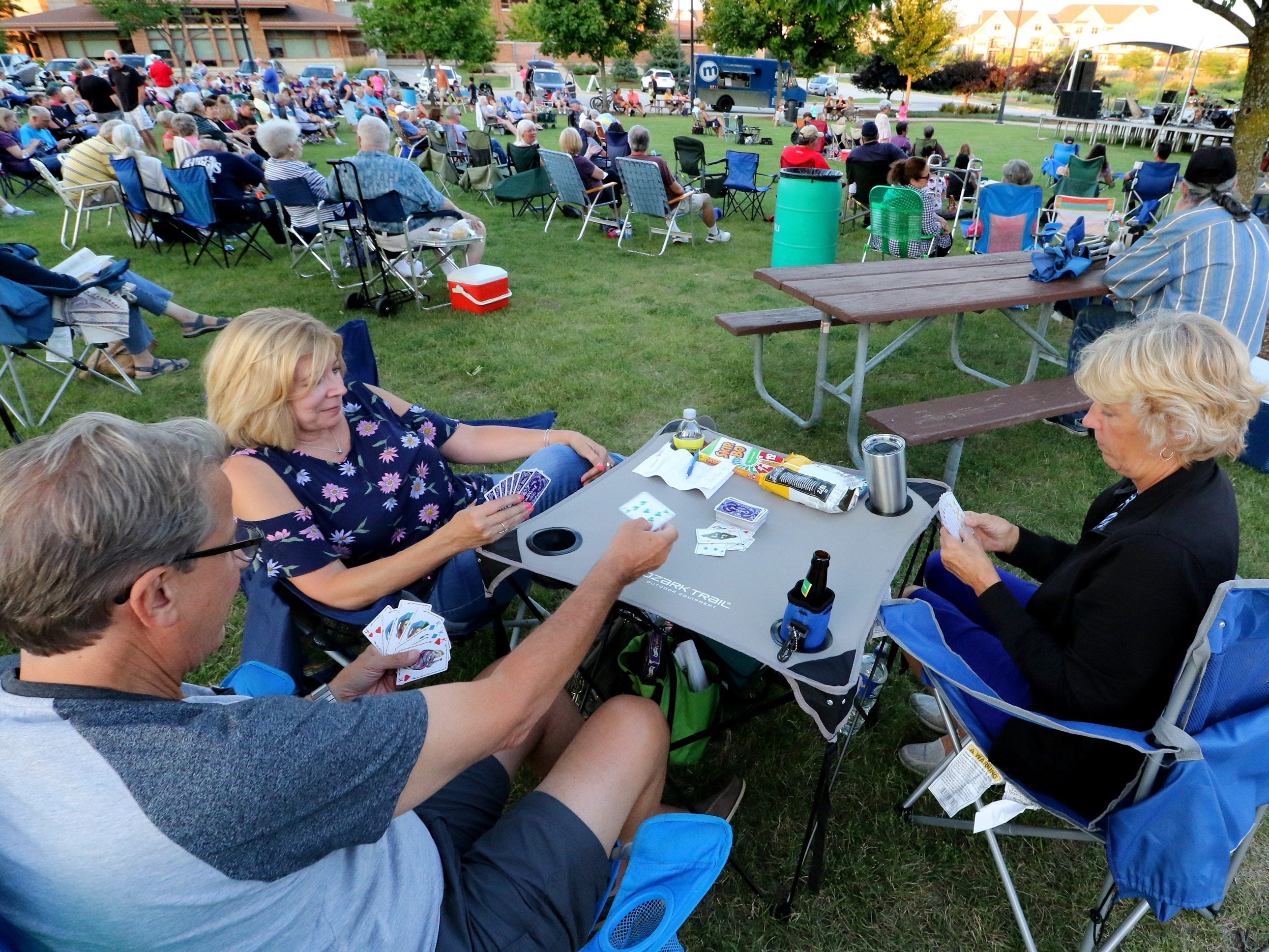 Don and Dawn Janczak of Genesee (left) and Wendy Petzold of Florida play the card game Five Crowns while listening to Streetlife with Warren Wiegratz at a New Berlin Concerts at City Center on Aug. 8.