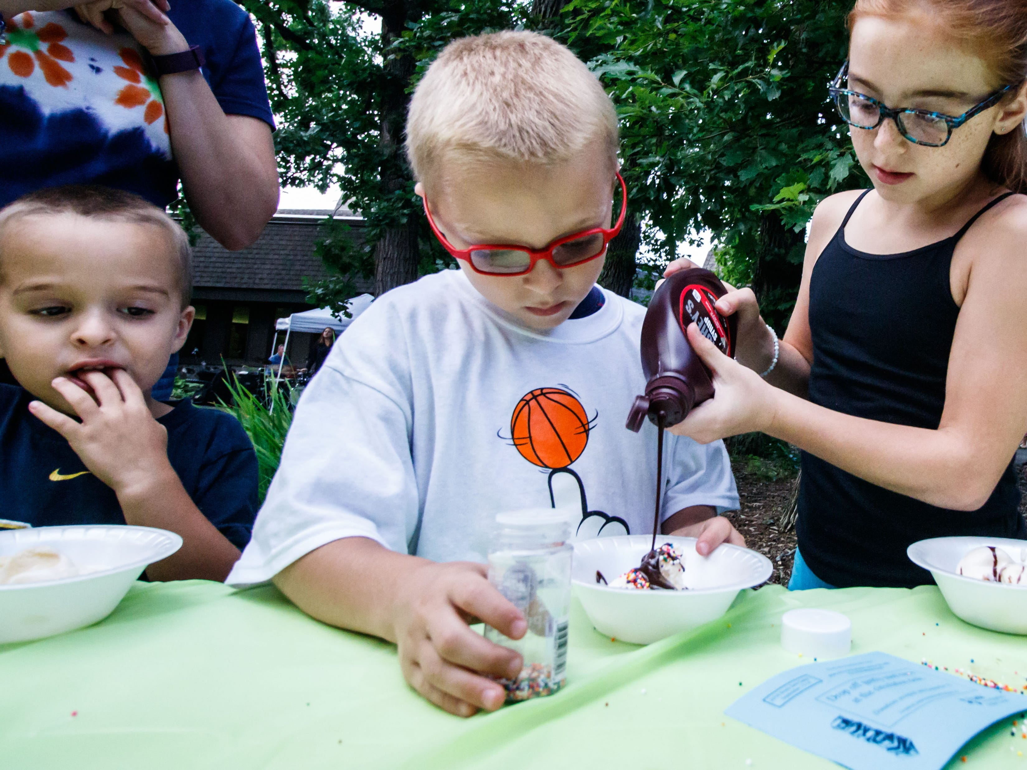 Four-year-old Anthony Stith, of Brookfield, looks on as his brother Thomas, 7, and sister Mary, 10, build the perfect sundae at the Brookfield Public Library's Ice Cream Social on Tuesday, August 7, 2018. The free event, sponsored by Friends of the Library, celebrates the end of Summer Reading with ice cream and music.