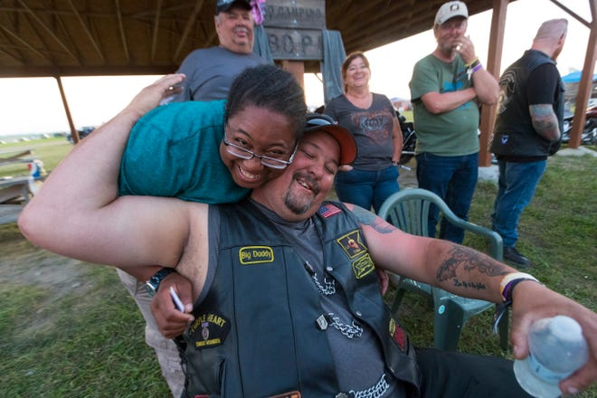 """Wounded Warrior members Kattathu Johnson and Harvey """"Big Daddy"""" Paige embrace after Paige talked about what it was like following her motorcycle with constantly blinking turn signal while hanging out with other veterans."""