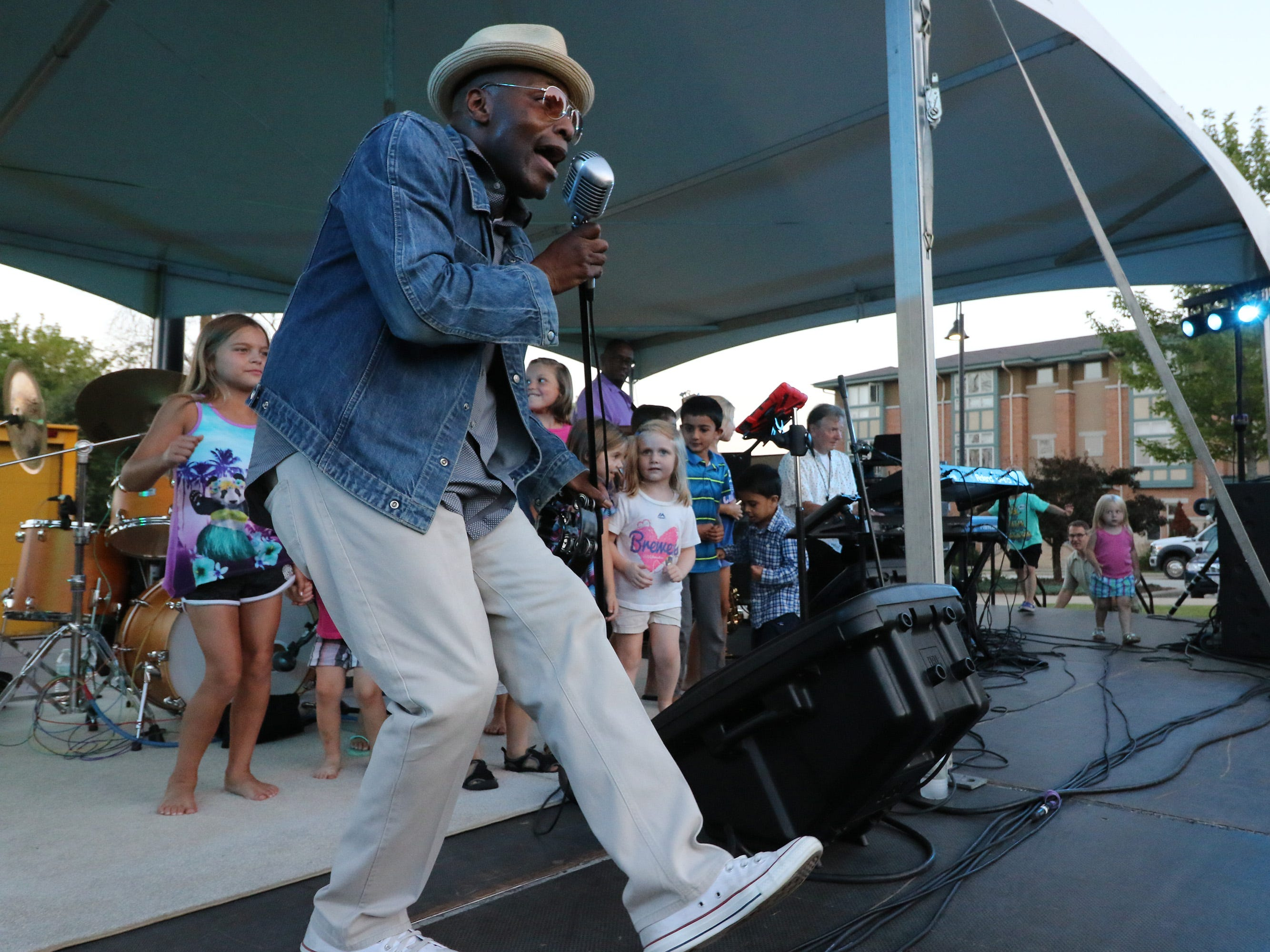 """Joe Jordan invites chilren onto the stage to dance with him as he sings """"Happy"""" with Streetlife with Warren Wiegratz at a New Berlin Concerts at City Center on Aug. 8."""